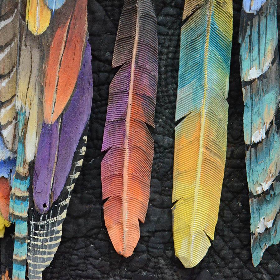 Détail de sculpture de plumes en bois peint